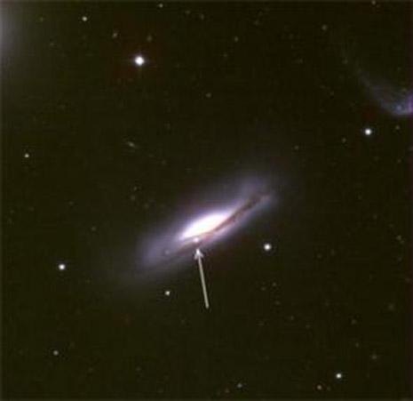 La freccia indica una supernova scoperta su una lontana galassia. Esplosioni di questo tipo creano oggetti talmente luminosi da competere addirittura con la luce dell'intera struttura che li contiene