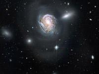 la NGC4911 con sullo sfondo alcune galassie ellittiche che già hanno subito la trasformazione