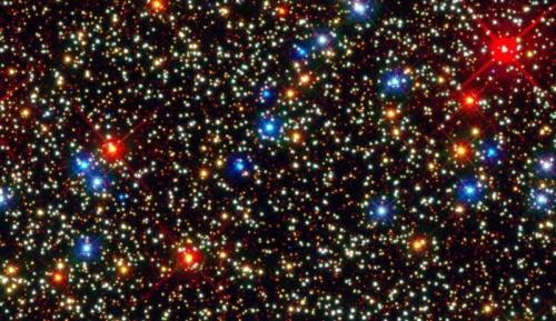 """L'ammasso di Omega Centauri: le stelle rosse (blu significa """"caldo"""", rosso """"freddo"""") sono proprio quelle che potrebbero in parte spiegare il disaccordo tra luminosità e massa. Esse sono visibili negli ammassi, relativamente vicini, ma non nelle galassie lontanissime e primordiali. (Fonte: NASA/ESA/Anderson/van der Marel)"""