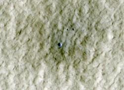 Al centro di questo quadro che raffigura una zona a media-latitudine nell'emisfero nord di Marte, un nuovo cratere di circa 6 metri di diametro (20 piedi) racchiude una esposizione di materiale più luminoso, rappresentato in blu in questa immagine a falsi colori. Credit: NASA/JPL-Caltech/University of Arizona